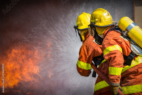 Photo 2 firefighters spraying high pressure water to  fire with copy space