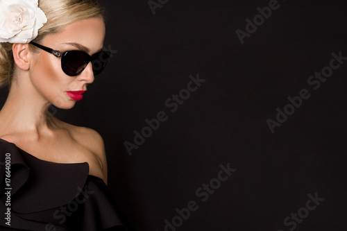 Spoed Foto op Canvas womenART Portrait of beautiful woman with stunning face with flower in hair and in elegant sunglasses, on black background