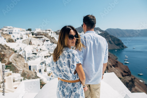 Fototapeta The couple is standing on the roof in Santorini, the girl turned to the camera obraz