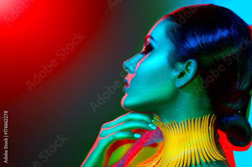 Foto op Plexiglas Beauty Fashion model woman in colorful bright lights with trendy make-up, manicure and haircut