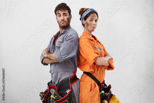 Portrait of confident handyman and his female colleague stand back to each other, keep hands folded, have dirty faces after repairing steps, wear special uniform and belt with tools. Maintenance