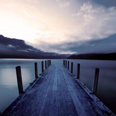 Panel Szklany Podświetlane Wschód / zachód słońca Boat jetty and a calm lake at sunrise, New Zealand.