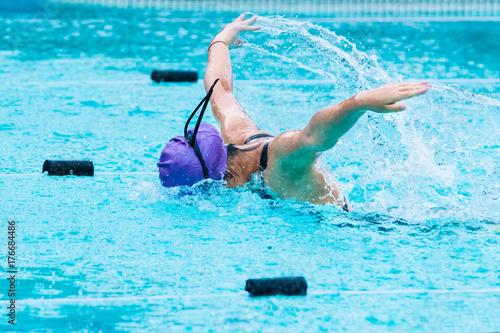 Plakat młoda kobieta pływak pływanie w skok motylkowy, podnoszenie jej broni wysoko, w basenie szkoły
