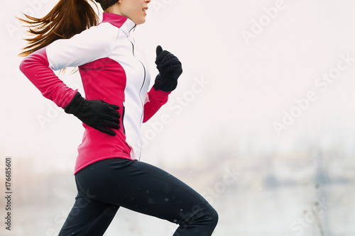 Poster Glisse hiver Winter running athlete woman on cold run jogging fast with speed and sprint on outside workout wearing warm clothing gloves, winter tights and wind jacket in snow weather.