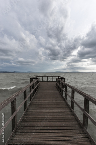 Foto op Plexiglas Panoramafoto s First person view of a pier on a lake on a moody day, with dark water and overcast, stormy sky