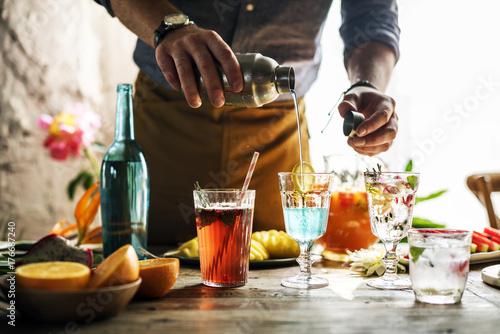 Obraz na plátně  Bartender mixing colorful cocktails