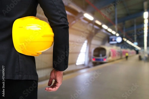 back view of engineer and holding yellow safety helmet standing in front of sky train at train station background, industrial, transportation and business concept