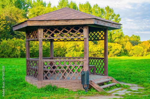 Photo Wooden arbour in park a background of green lawn and trees