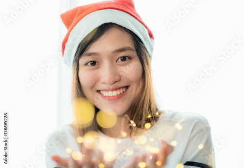 Fotografering  smiling asia woman wear santa hat holding party string lights with bokeh light at Christmas party,Holiday celebration concept,sparkling light decoration,make a wish