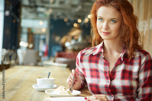 Foto  Young  beautiful woman in glasses reading interesting book in cafe