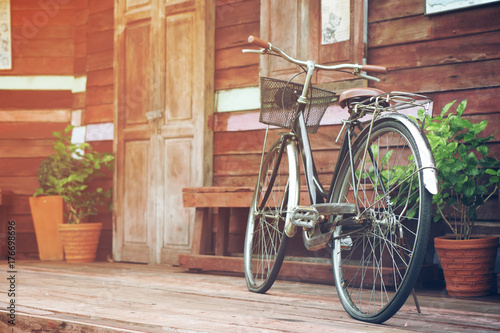 Poster Fiets vintage old black and brown bicycle or bike at front of retro wood home terrace with wood door and window with tree in flowerpot for interior architecture decor or past memory background with sunlight