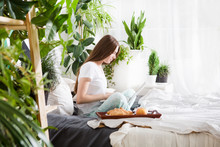 Beautiful Young Girl  Working On A Laptop Sitting On The Bed In The House.Breakfast In Bed For Young Beautiful Woman