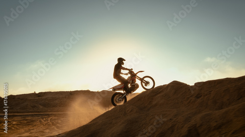 Photo  Side View Footage of the Professional Motocross Motorcycle Rider Driving on the Dune and Further Down the Off-Road Track