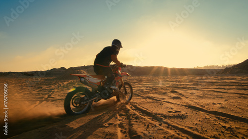 Shot of the Professional Motocross Driver Riding on His FMX Motorcycle on the Extreme Off-Road Terrain Track.