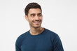 Leinwandbild Motiv Close up portrait of smiling handsome male in blue t-shirt looking right, isolated on gray background