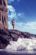 beautiful girl standing on rocky shore