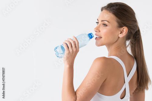 Woman drinking water from blue bottle