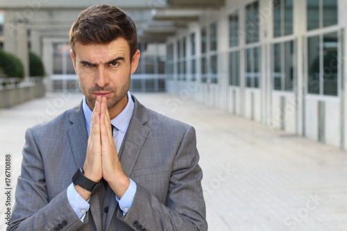 Evil businessman praying in the office Tablou Canvas
