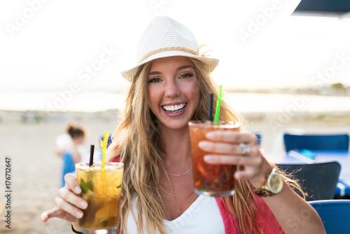 Zdjęcie XXL Piękna młoda kobieta pije orzeźwienie na plaży.