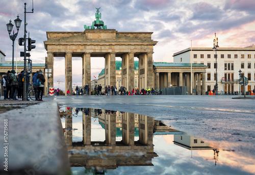 Poster Berlin Das Brandenburger Tor in Berlin mit Spiegelung im Regenwasser bei Sonnenuntergang