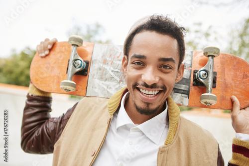 Fototapeta Szczęśliwy młody mężczyzna deskorolkarz jest rozkoszny po spędzeniu rano w sobotę na zewnątrz, jeździ na deskorolce, uśmiecha się radośnie, poprawia umiejętności jazdy. Sportowy nastoletnia łyżwiarz z radosnym wyrazem