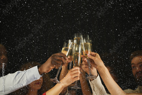 Fényképezés Group of young people celebrating new year with champagne at night club