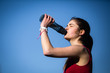 Beautiful blonde girl drinking water from a bottle after running. Shot outdoors. Blue background