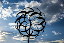 Garden Whirligig Silhouetted Against A Blue Cloudy Sky