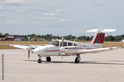 Plakat czerwony biały i niebieski podwójny śmigłowy samolot stacjonarny na płycie lotniska