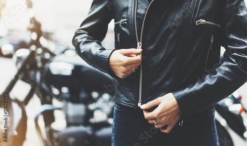 Fototapeta czarna skórzana kurtka na tle motocykla w słońcu rozbłyszcza atmosferyczne miasto, hipster rowerzysta kobieta ręce zbliżenie, motocykl ulica styl życia, podróżnik strugania trasa rowerowa w letnie wakacje koncepcja