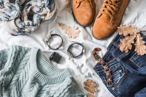 Zdjęcie XXL Płaskie leżała odzież damska na jesienne spacery, widok z góry. Brązowe zamszowe buty, dżinsy, niebieski pulower, szalik, bransoletki, zegarki, słuchawki, perfumy na jasnym tle. Koncepcja mody