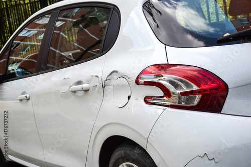 Photo  A car with a scratch on the body. Close-up