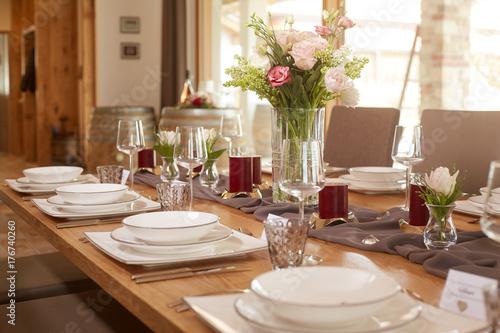 Zdjęcie XXL Stołowa dekoracja z wiązką kwiaty i czerwone świeczki na popielatym stołowym biegaczu na drewnianym stole w dużej otwartej przestrzeni. Zakryte są klasyczne mądre naczynia.