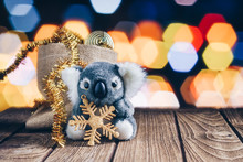 Cute Koala Decorated With Christmas Decoration Items On Wood And Bokeh Background
