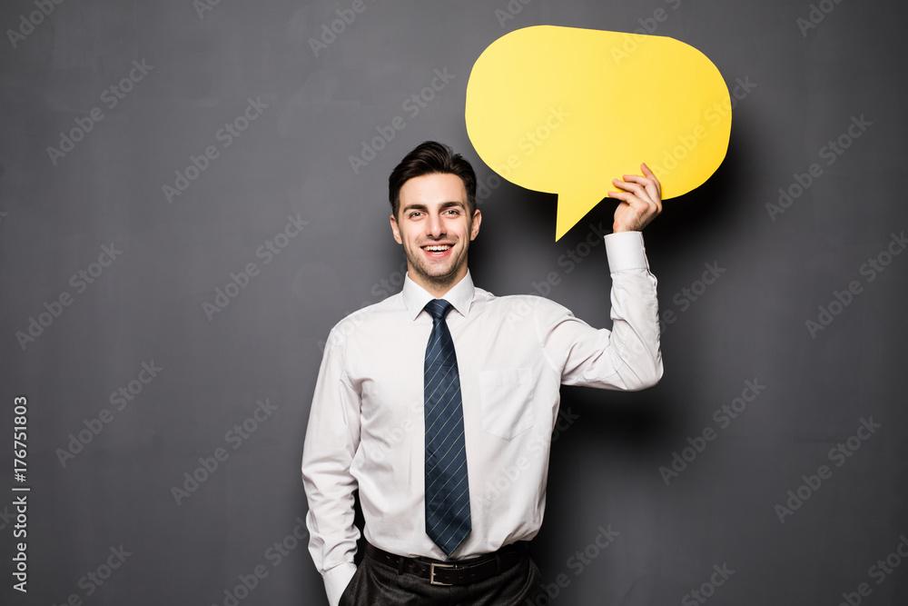 Fototapeta Businessman holding Speech Bubble on gray background