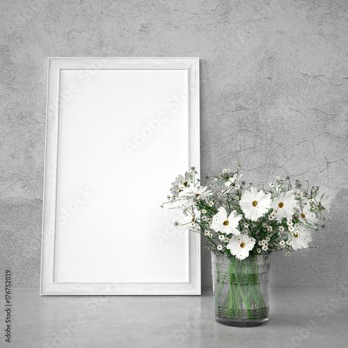 Zdjęcie XXL Bukiet obok białej drewnianej ramy obrazu przed ścianą