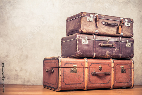 Vintage old classic big travel leather suitcases on wooden floor. Travel luggage concept. Retro instagram style filtered photo