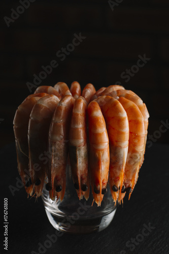 Staande foto Vlees Shrimps on black background. Delicious seafood appetizer served boiled or grilled with spices. Close up. Top view