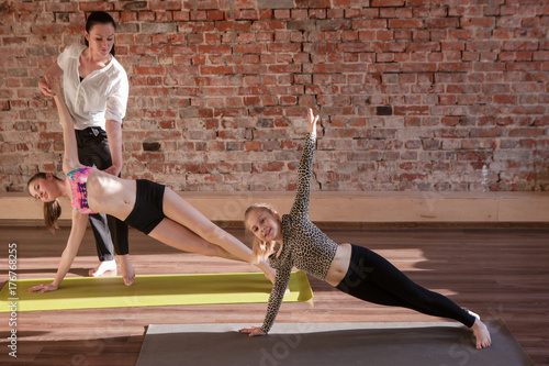 Tuinposter Gymnastiek Gymnastics exercises. Healthy children lifestyle. Teenage sport with female instructor, yoga for kids. Happy stretching girls in studio. Gym wall background with free space, health concept