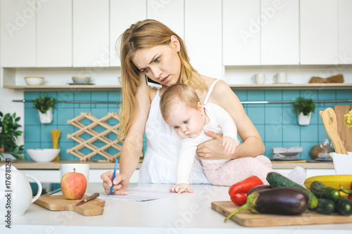 Foto  Young mother with her baby daughter in a modern kitchen setting