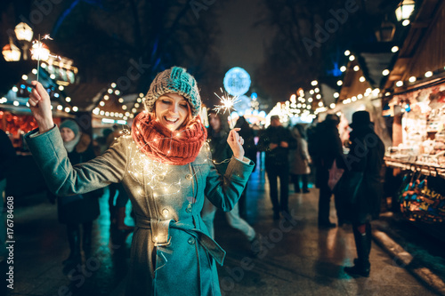 Fotografía  Outdoor photo of young beautiful happy smiling girl holding sparklers, posing in street