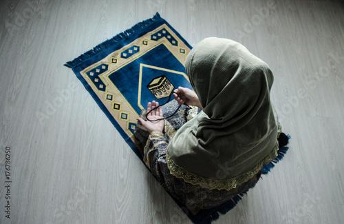 Fototapeta Muzułmańska kobieta modli się za Allaha muzułmańskiego boga przy izbowym pobliskim okno. Ręce muzułmańskiej kobiety na dywanie modląc się w tradycyjne stroje, Kobieta w Hidżab, dywan z Kaaba, Selektywne focus