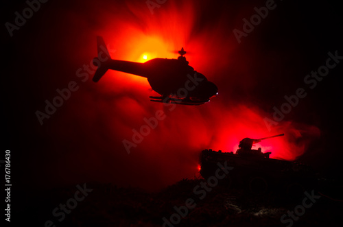 Plakat Zakamuflowany wojskowy helikopter w locie przeciwko dramatycznemu czerwonemu niebu. Ciężka zbroja na polu walki. Ciemne pochmurne niebo