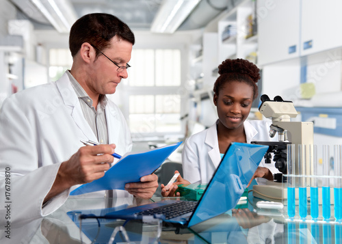 Fényképezés  Scientists, Caucasian male and African female, work in laboratory
