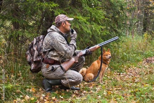 hunter with a grouse call and shotgun