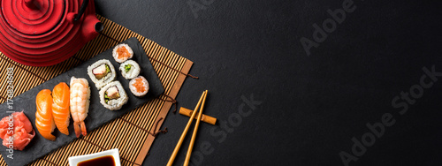 Tuinposter Sushi bar Set of sushi with wasabi, soy sauce and teapot on black stone background