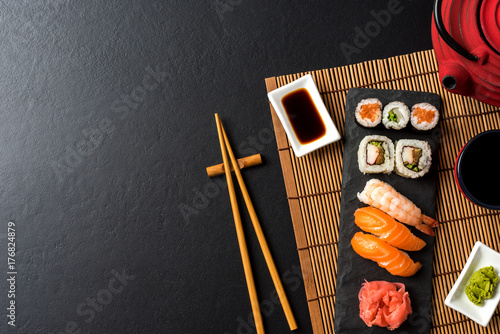 Poster Sushi bar Set of sushi with wasabi, soy sauce and teapot on black stone background