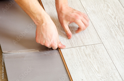 Handymans Hands Laying Down Laminate Flooring Boards Buy This