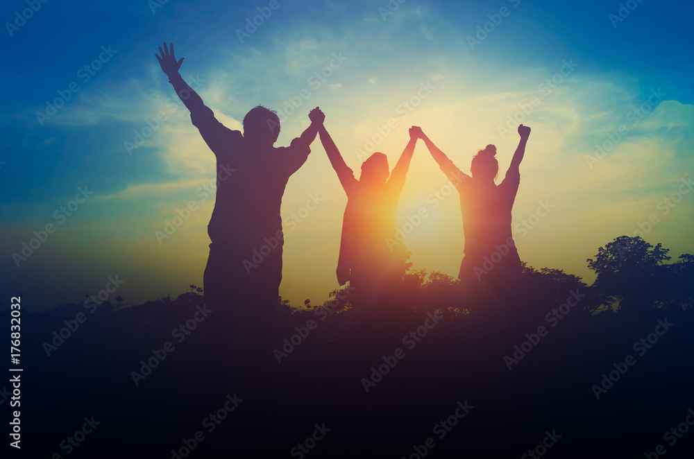Fototapeta Silhouette of happy teamwork hold hands up as a business successful, business victory