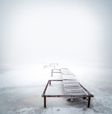 Stary drewniany gangway na zamarzniętym jeziorze przy zima sezonem - 176832834